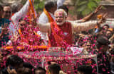 Supporters throw flower petals as Bharatiya Janata Party (BJP) leader Narendra Modi rides in an open jeep on April 9, 2014 in Vadodra, India.