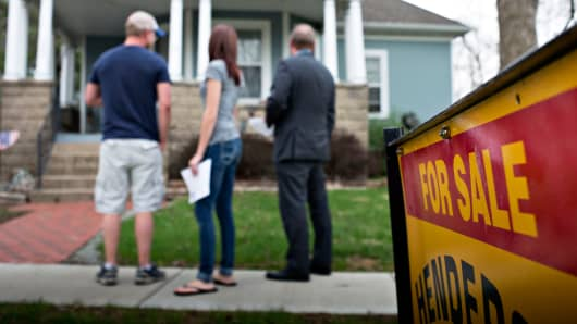 An agent, right, stands with potential home buyers outside a previously owned home in Mackinaw, Illinois, Monday, April 21, 2014.