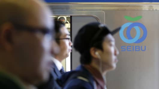 Passengers walk past the Seibu Railway Co. logo displayed on a train at a train station in Tokyo, Japan.