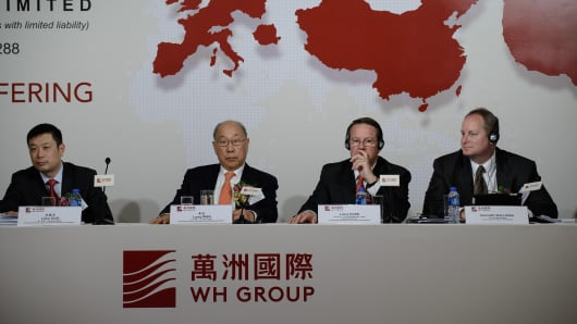 (L to R) Chief financial officer of WH Group, Guo Lijun, Executive director and chairman of WH Group, Wan Long, Executive director and president of Smithfield, Larry Pope, Smithfield chief financial officer, Kenneth Sullivan attend a press conference in Hong Kong.