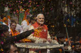 Flower petals are thrown around Bharatiya Janata Party (BJP) leader Narendra Modi as he rides in an open jeep on his way to file nomination papers on April 9, 2014 in Vadodra, India.
