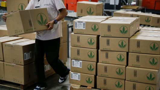 An employee carries a box of products for shipment to a truck at the Herbalife Los Angeles distribution center in Carson, Calif.