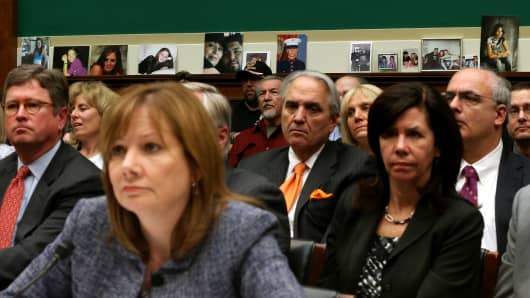Pictures of people killed in GM cars with defected key switches, were put of the ledge of the hearing room as General Motors Company CEO Mary Barra (L) answers questions during a House Energy and Commerce Committee hearing on Capitol Hill, on April 1, 2014 in Washington, DC.