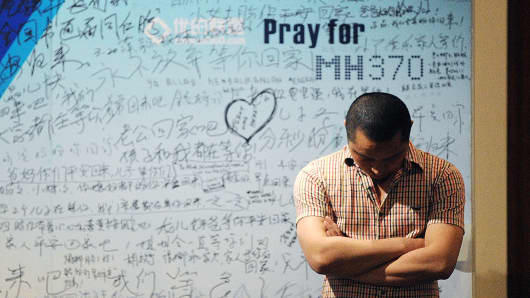 A man stands in front of a billboard in support of missing Malaysia Airlines flight MH370 as Chinese relatives of passengers on the missing Malaysia Airlines flight MH370 have a meeting at the Metro Park Hotel in Beijing.