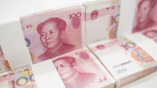 Chinese one-hundred yuan banknotes are arranged for a photograph at a Standard Chartered Plc bank branch.