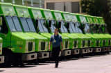 A man walk past an Amazon Fresh trucks parked at a warehouse in Inglewood, Calif.