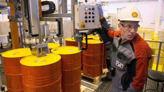 An employee holds a control panel as barrels are filled with lubricant oil for shipping at Royal Dutch Shell Plc's plant in Torzhok, Russia, March 21, 2014.