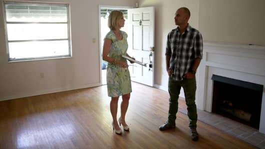 Real estate agent, left,  shows prospective buyer a home on April 22, 2014 in Coral Gables, Florida.