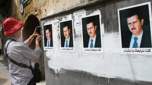 A tourist takes pictures of a wall decorated with posters of Syrian President Bashar al-Assad in the old city of Damascus