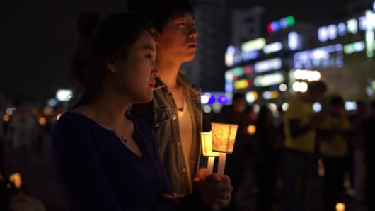 People hold candles at a vigil for students among the missing passengers of a South Korean capsized ferry, April 26, 2014.