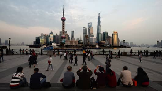 Chinese and foreign tourists view the Pudong financial district skyline from the historic Bund in Shanghai.