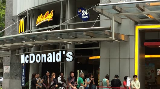 A queue forms outside of a McDonald's branch in Singapore on April 28, 2014.