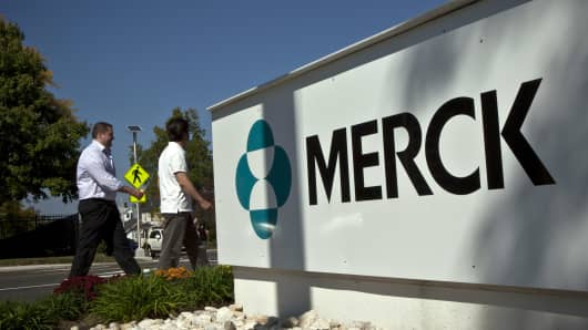 Merck employees walk past a Merck sign in front of the company's building in Summit, New Jersey.