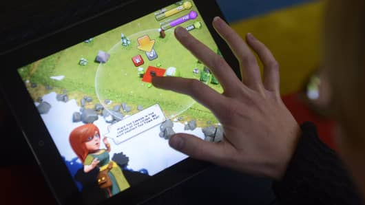 "A woman plays the ""Clash of Clans"" from computer game maker Supercell on a tablet computer."