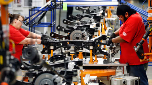 Employees work on the axle of a 2015 Chrysler 200 at the company's Sterling Heights Assembly Plant in Sterling Heights, Michigan, March 14, 2014.