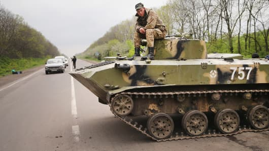 Ukrainian soldiers guard a roadblock along the highway on
