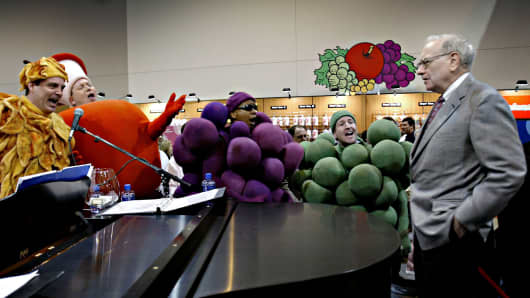 Warren Buffett listens to a performance at the Fruit of the Loom booth in the exhibition area of the Berkshire Hathaway annual meeting in Omaha, Nebraska, in 2005.