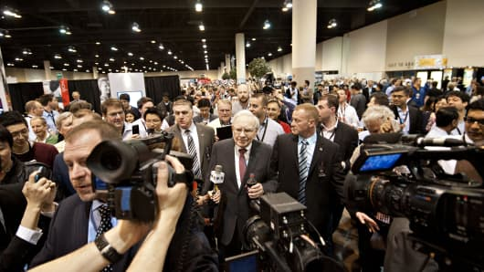 Warren Buffett, chairman of Berkshire Hathaway Inc., center, tours the exhibition floor prior to the Berkshire Hathaway shareholders meeting.