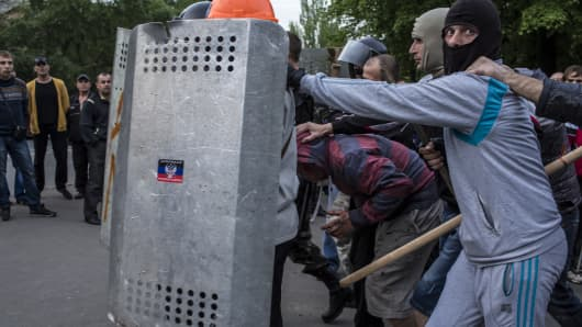 Pro-Russian protesters detain a man who was beaten and accused of being a provocateur outside the Executive Council building