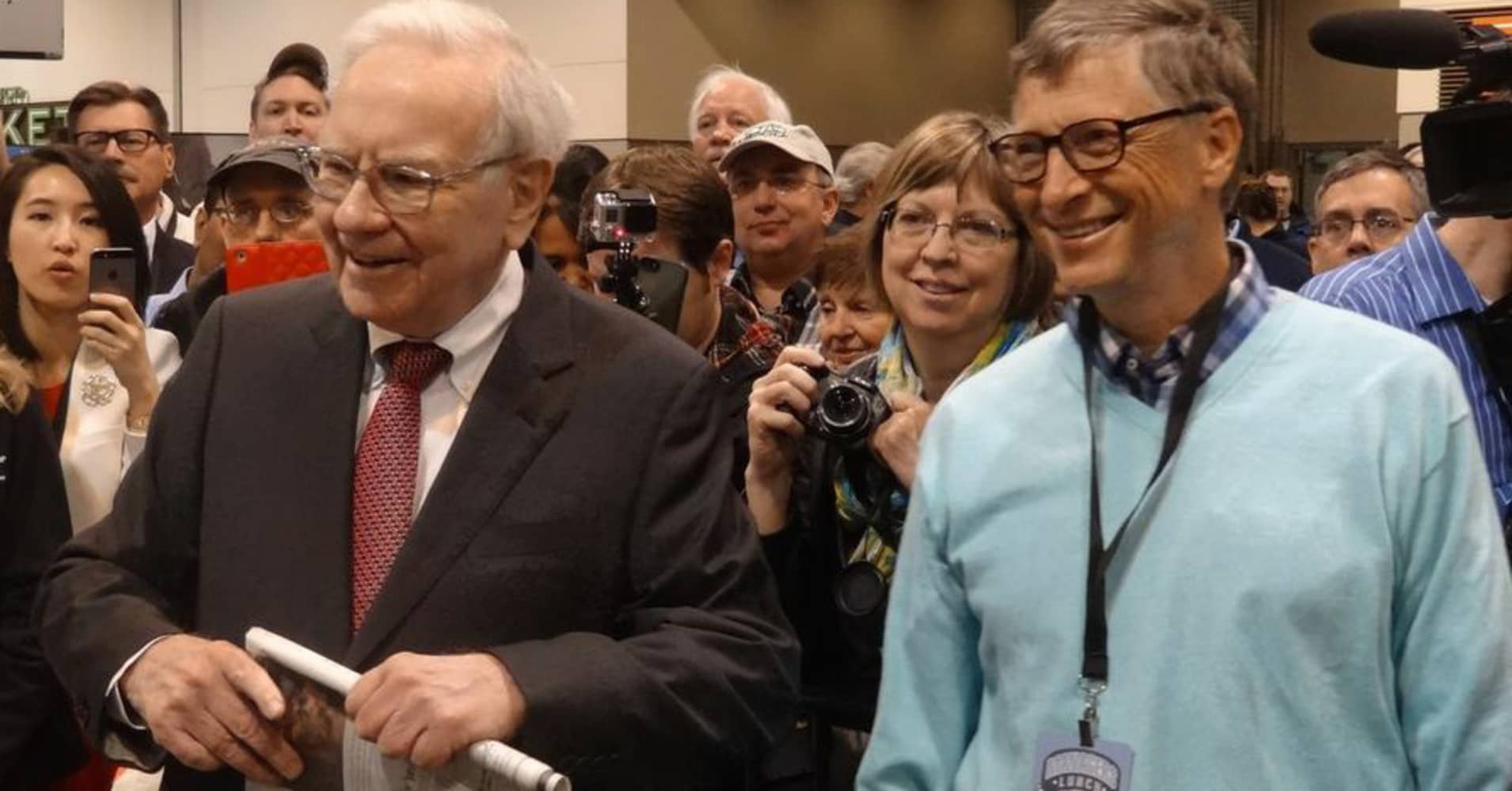 Warren Buffett and Bill Gates prepare to do the 'newspaper toss' at the Berkshire Hathaway Annual Shareholder's Meeting in Omaha, Nebraska.