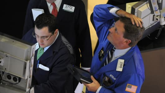 A trader on the floor of the New York Stock Exchange looks at stocks during the final minutes of trading May 6, 2010 as the Dow lost almost 1,000 points before recovering to a loss of 505.