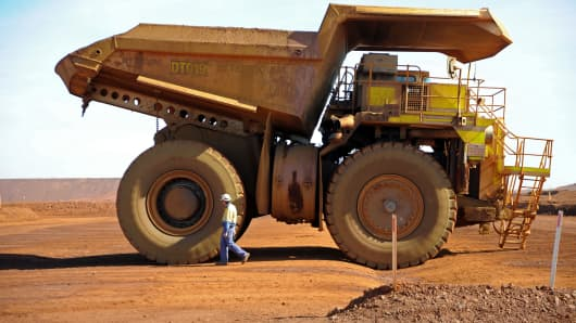 A driver inspects an earth mover at Fortescue Metals Group Ltd.'s Cloudbreak iron ore operation in the Pilbara region of Western Australia, on Monday, July 25, 2011