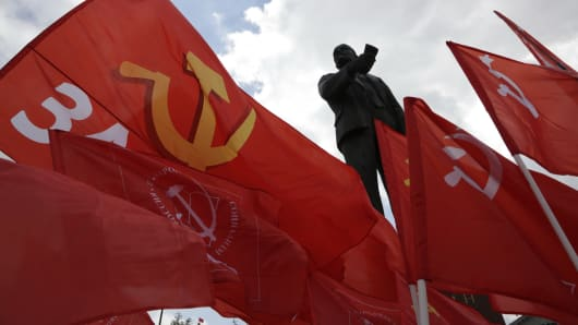 Communist party members and supporters hold their red flags near a monument to the Soviet Union founder Vladimir Lenin in the Crimean capital Simferopol, on May 6, 2014.