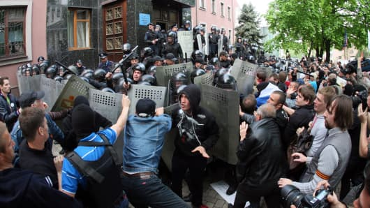A crowd of some 300 pro-Russian separatists clash with riot police as they storm the prosecutor's office in the eastern Ukrainian city of Donetsk on May 1, 2014.