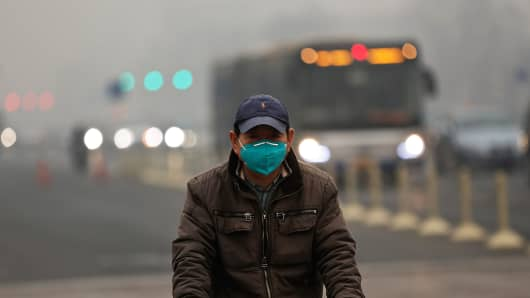 A man wearing a mask rides a bicycle during severe pollution on February 25, 2014 in Beijing, China.