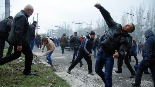 Pro-Russia protesters throw stones as they storm a regional police building in the eastern Ukrainian city of Horlivka (Gorlovka), near Donetsk, on April 14, 2014.