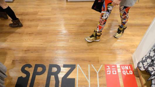A shopper walks over some floor branding at the Uniqlo fashion boutique in Melbourne, Australia.