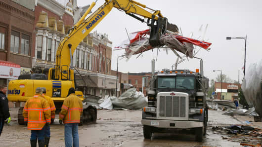 Debris is cleared from downtown Sutton, Neb., Monday, May 12, 2014, after a tornado touched down in town on Sunday.