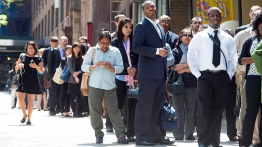 Job seekers line up outside at Choice Career Fairs' New York career fair in New York, May 13, 2014.