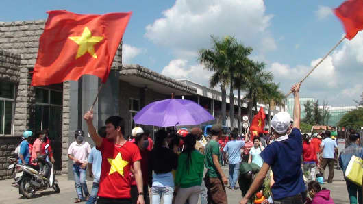 protesters wave Vietnamese flags as they rally on a street outside a factory building in Binh Duong, as anti-China protesters set more than a dozen factories on fire in Vietnam, according to state media, in an escalating backlash against Beijing's deployment of an oil rig in contested waters.