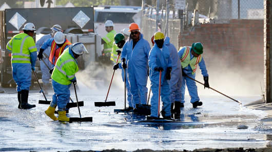 Workers clean up an oil from a pipe that burst causing about 10,000 gallon of crude oil spill onto streets covering an area of about a half-mile, May 15, 2014, in Los Angeles.