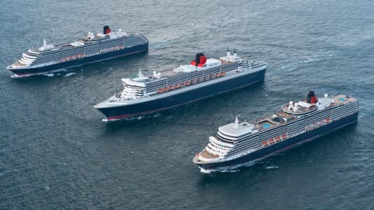 Queen Mary 2, center, and her sister ships Queen Elizabeth and Queen Victoria sail in formation.