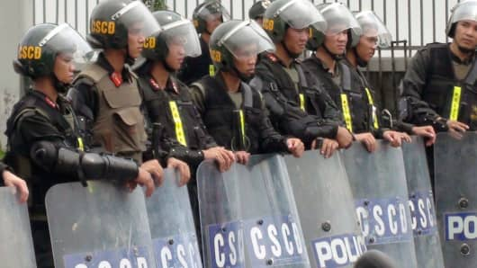 Riot police stand guard on a street outside a factory building in Binh Duong