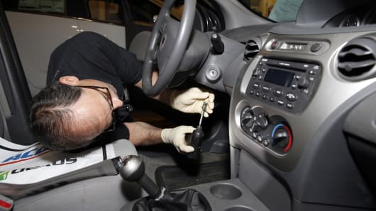 Shop foreman John Chapman performs a service recall on a General Motors 2005 Saturn Ion at Liberty Chevrolet in New Hudson, Michigan, U.S., on Friday, April 25, 2014.