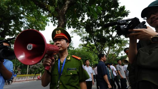 A policemen use a megaphones asking people not to gather on a street near to the Chinese embassy in Hanoi.