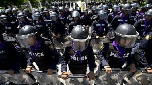 Thai riot police stand guard during an anti-government protest rally at the Air Force auditorium in Bangkok on May 15, 2014.
