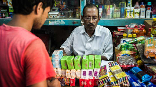 A shopkeeper serves a customer in a local grocery store in the Kalahati market area in Siliguri, West Bengal, India. India's small shop owners are a voting block with real clout in India.