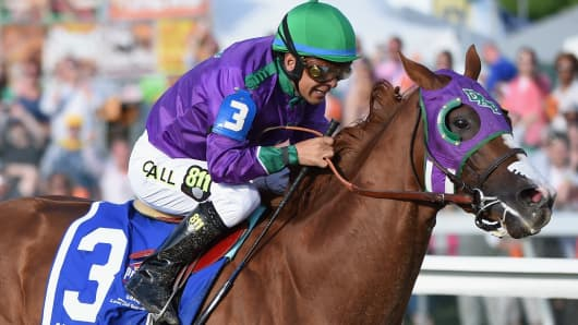 California Chrome #3, ridden by Victor Espinoza, races to the finishline to win the 139th running of the Preakness Stakes at Pimlico Race Course on May 17, 2014 in Baltimore, Maryland.