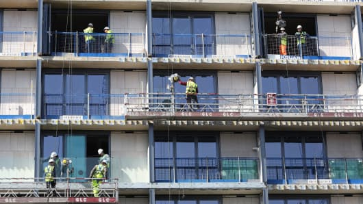 Construction workers stand on apartment balconies at the Lexicon residential building site in London, UK