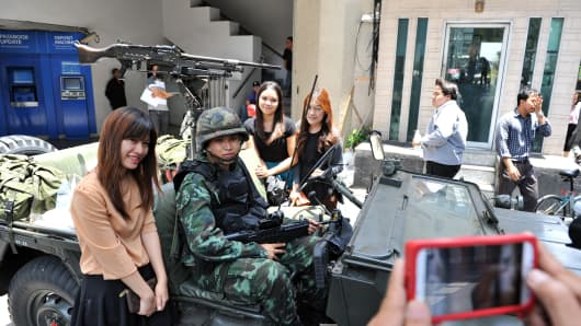 Passersby pose for a photo with Thai soldiers standing guard on a Bangkok street after martial law was declared on May 20, 2014.