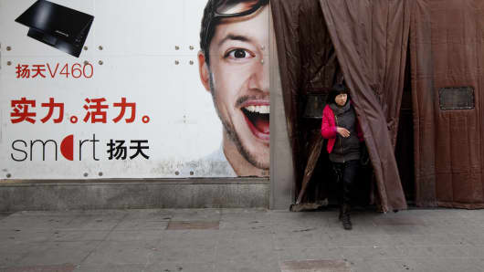 A woman exits past an advertisement for Lenovo Group Ltd. at a computer market in Beijing, China, on Thursday, Feb. 17, 2011. Lenovo Group Ltd., China's biggest maker of personal computers, is expected to announce third-quarter earnings today.