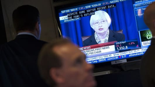 Traders watch Janet Yellen, chair of the U.S. Federal Reserve, speak on during a news conference.