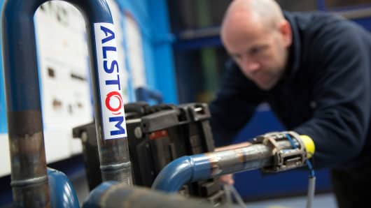 An Alstom welding instructor uses a sound wave sensor to test for defects in welded metal joints at Alstom SA's welding training facility in Stafford, U.K., May 12, 2014.