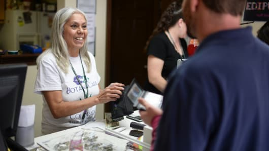 Lorraine Cendejas of Botana Care, left, helps customers purchasing recreational marijuana. Northglenn, Colorado. May 16. 2014.