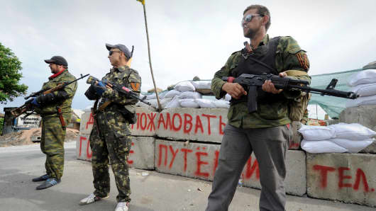 Pro-Russian armed militants stand guard at a barricade which faces a position manned by Ukrainian army soldiers near the eastern Ukrainian city of Slavyansk, Donetsk region, on May 23, 2014.