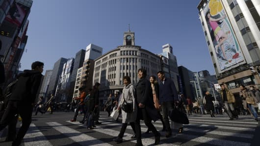 Pedestrians cross a street in the Ginza district of Tokyo, Japan.